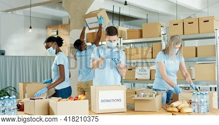 Caucasian And African American Males And Females Packing Donated Food Preparing Donations Boxes In S