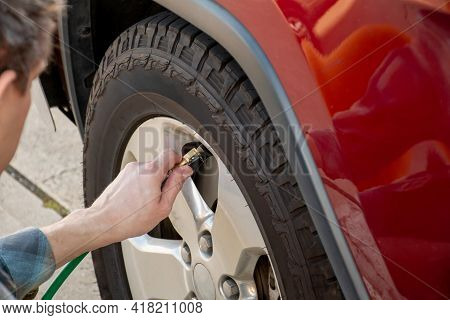 Man Holding Pump Pressure Gauge, Checking Air Pressure And Filling Air In The Tires Of The Car. Car