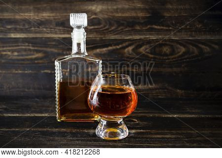 Glass Flacon And Wineglass With Cognac On Wooden Plank Surface
