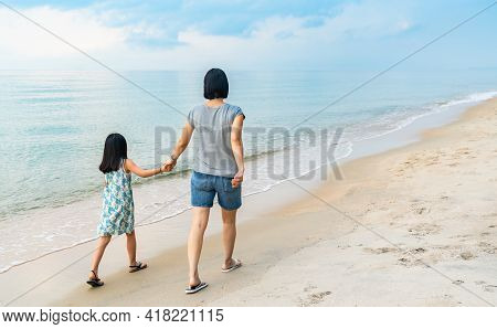 Back View Of Asian Mother And Little Daughter Are Walking Forward On The Beach, Active Image With Mo