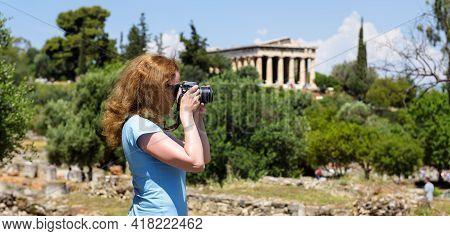 Girl Tourist Takes Photo Of Athens, Greece, Europe. Temple Of Hephaestus, Landmark Of Athens In Dist