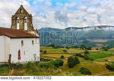 Ancient Church With Bell Tower In The Green Field With High Mountains In The Background. Asturias Sp