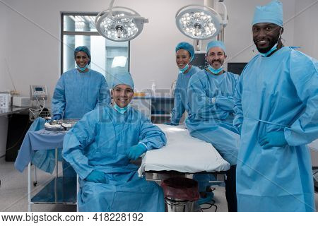 Smiling diverse surgeons with face masks and protective clothing in operating theatre. medicine, health and healthcare services during covid 19 coronavirus pandemic.