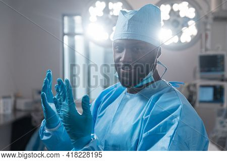 Smiling african american male surgeon with face mask in protective clothing in operating theatre. medicine, health and healthcare services during covid 19 coronavirus pandemic.