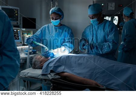 Diverse surgeons with face masks and protective clothing during operation, sedating patient. operating theatre. medicine, health and healthcare services during covid 19 coronavirus pandemic.