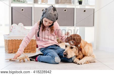 Little girl in hat playing with wooden plain and golden retriever dog in pilot glasses lying next to her