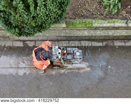 Worker Cutting Asphalt With Hand Managed Equipment. Luxembourg, Luxembourg - March 5, 2021.
