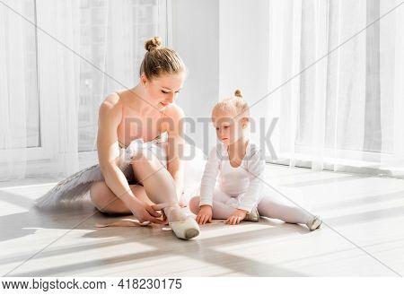 Ballet teacher sitting on the floor with little ballerina and teaching how to tie ballet pointe shoes. Little girl sitting on the floor with her mother and helping her to tie ballet shoes