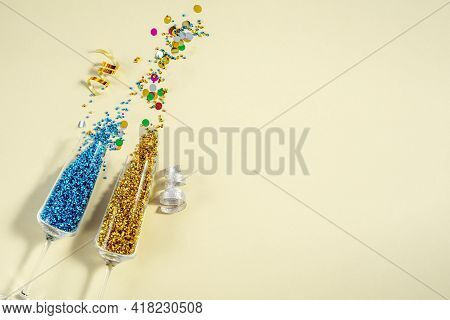Pair Of Festive Wine Glasses With Shiny Tinsel, Confetti And On Cream Color Background, Top View. Pa