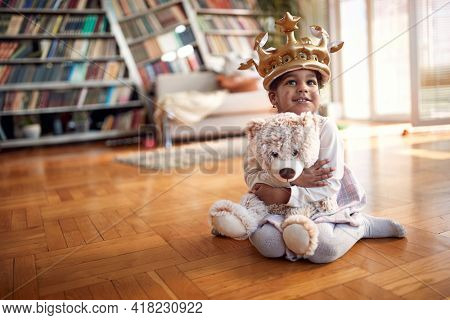 A cute little girl with sweet smile posing for a photo on the floor in a relaxed atmosphere at home. Family, together, love, playtime