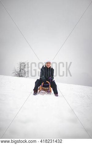 Teenager With A Smile On His Face Sits On A Wooden Historic Sledge And A Ride At The Hill He Managed