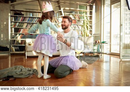 A young Dad helping his little daughter about ballet training in a relaxed atmosphere at home. Family, together, home