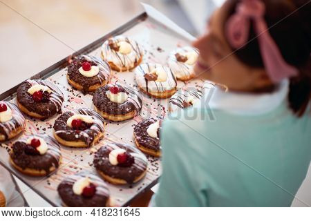 A young small business female owner is satisfied about of handmade delicious donuts of irresistibility appearance ready for a pastry shop. Pastry, dessert, sweet, making