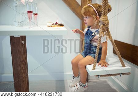 A little girl is sitting in a pastry shop and enjoying delicious donuts of irresistible appearance. Pastry shop, dessert, sweet
