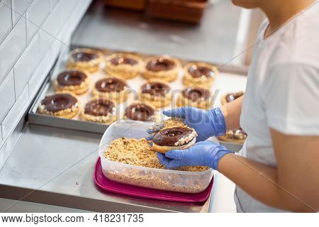 A worker making delicious donuts in a working atmosphere in a candy workshop. Pastry, dessert, sweet, making