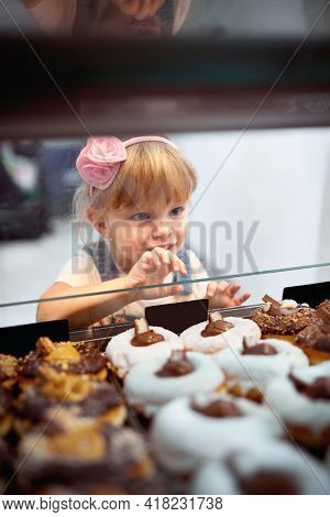 A little girl passionately looking at delicious donuts of irresistible appearance in a showcase in a pastry shop. Pastry, dessert, sweet