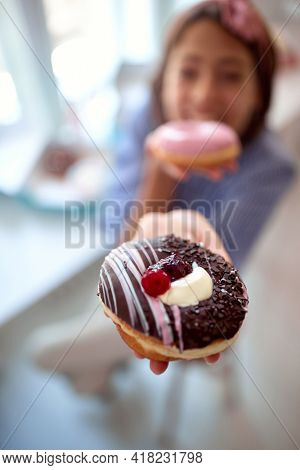 Closeup of a donut held by beautiful young girl in a pleasant atmosphere in a pastry shop. Pastry shop, dessert, sweet