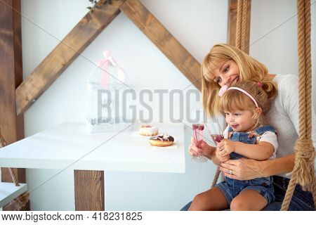 A little girl is enjoying a drink and delicious donuts of irresistible appearance while sitting in her mother's lap in a pastry shop. Pastry shop, dessert, sweet