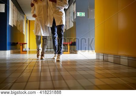 A young student couple in a hug is enjoying a break at the university building hallway in a relaxed atmosphere. Institution, hallway, university, people