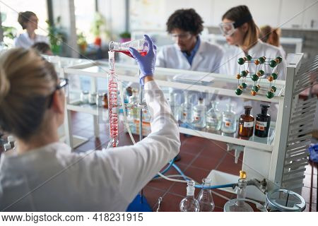 Young chemistry students working on an experiment in a laboratory in a working atmosphere. Science, chemistry, lab, people