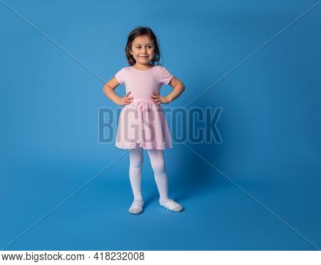 Little Ballerina In Pink Dress Posing Into The Camera With Arms On Waist Over Blue Background With S