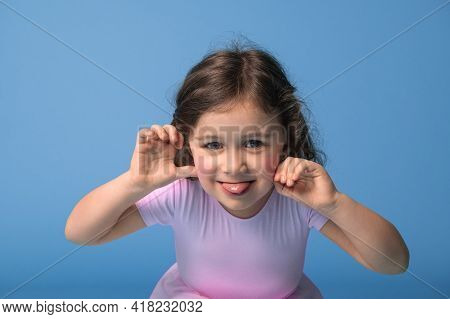 Face Portrait Of Preschool Girl In Pink Dress, Grimacing Looking At Camera, Isolated Over Blue Backg