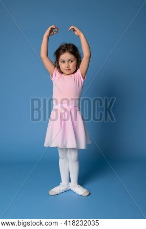 A Graceful Little Ballerina Performing Poses In Ballet Dance, Standing Isolated Over Blue Background