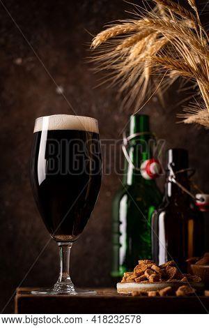Glass Of Dark Beer With Foam Head On Dark Wooden Background With Empty Bottles And Beer Snacks