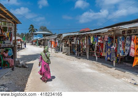 Zanzibar, Tanzania - February 8. 2020: Street View With A Woman And Shops In The Fishing Village Of