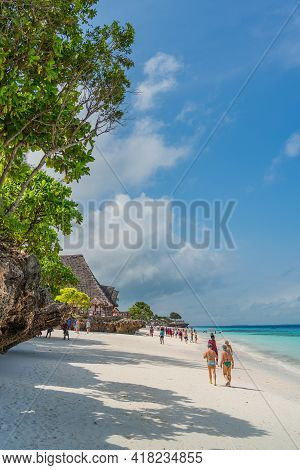 Zanzibar, Tanzania - February 12, 2020 : People At The Tropical White Beach With Turquoise Ocean Of