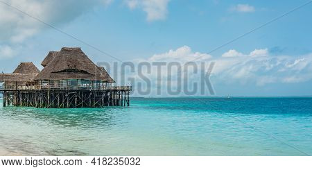 Zanzibar, Tanzania - February 12, 2020 : Tropical White Beach Of Zanzibar Island With A Thatched Roo