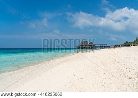 Zanzibar, Tanzania - February 12, 2020 : People At The Tropical White Beach With A Thatched Roof Bui