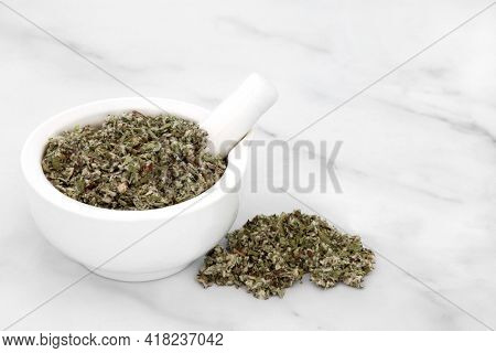 Coltsfoot herb leaves in a mortar with pestle used in herbal medicine to treat inflammation, asthma, gout, arthritis and coughs. On marble background. Asteraceae.