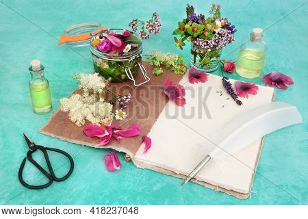 Natural herbal medicine for alternative remedies with flowers and herbs steeping in a jar with oil to make aromatherapy essential oil with hemp notebook and quill pen. Naturopathic health care.