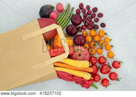 Immune boosting fruit and  vegetables for good health high in lycopene, anthocyanins, antioxidants, vitamins, minerals and dietary fibre. In a paper carrier bag and loose on mottled grey background.