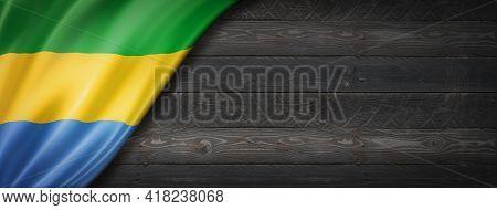 Gabon Flag On Black Wood Wall. Horizontal Panoramic Banner. 3d Illustration