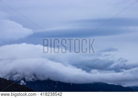 View Of Puffy Clouds Over The Canadian Mountain Landscape. Colorful Winter Sunset Cloudscape Backgro