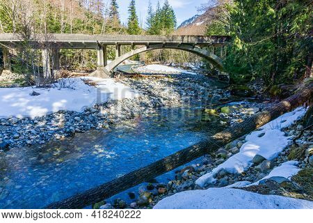 Denny Creek With Snow  On The Shore Flows Under A Bridge.