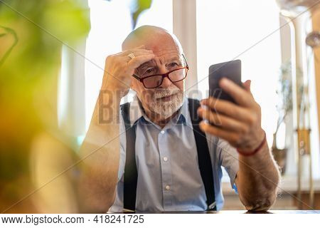 Senior man staring at his smartphone in confusion