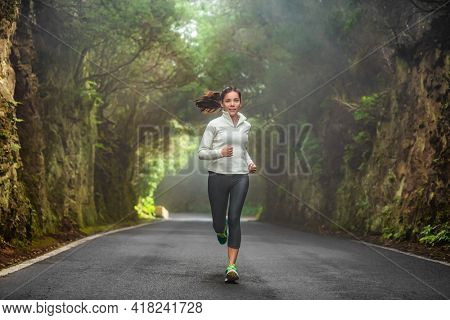 Running woman in autumn forest training on cold morning. Outdoor sport Asian girl athlete runner jogging outside fitness winter motivation.