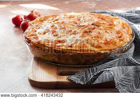 Homemade Baked Lasagna In Round Glass Baking Dish On Wooden Board