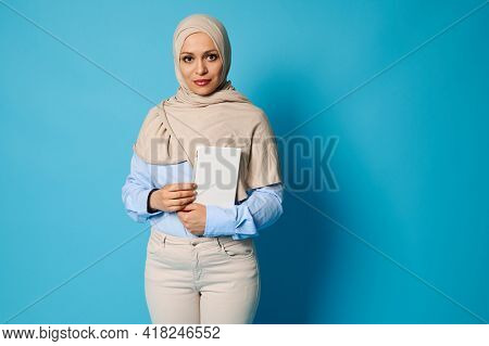 Serious And Serene Arab Muslim Woman With A White Book In Her Hands. Education Concepts On Blue Back