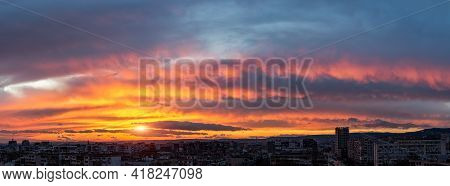 Dramatic Sunset Fire In The Sky Over A Small City. Evening Sun Is Low On The Horizon. Panoramic Land