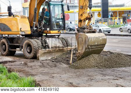 A Road Excavator Bucket Evenly Distributes Rubble To Create A Foundation On A Road Section Under Rep