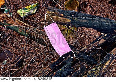 A Medical Mask Hangs On A Tree In The Park. Discarded Used Medical Masks. Contamination By Surgical