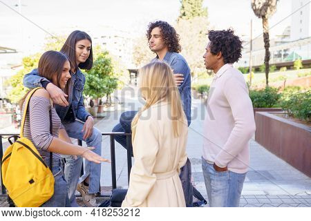 Multi-ethnic Group Of Friends Gathered In The Street Leaning On A Railing.