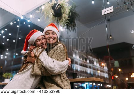 Portrait Of Happy Cute Young Friends Hugging Each Other At Caffe.