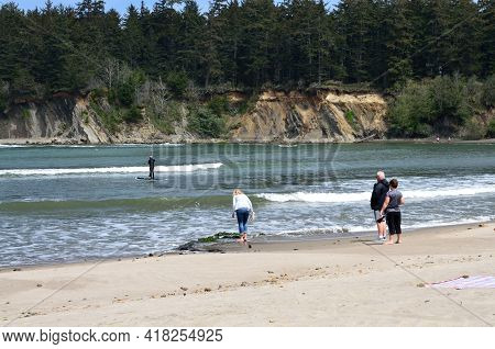 Group Of People Standing At The Surf Line Watching Paddle Boarder Surfing