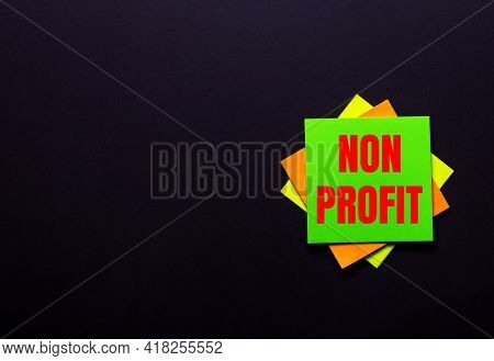The Words Non Profit On A Bright Sticker On A Dark Background. Copy Space