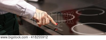 Female Finger Presses Button On Touch Electric Stove
